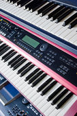 Electronic music synthesizer keyboards on rack — Stock Photo