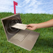 Laptop computer and hand with letter on grass — Stock Photo