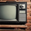 Retro grunge tv against brick wall. - Stock Photo