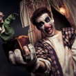 Photo of a scary clown holding a Jack-in-the-box toy - Stock Photo