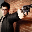 Man with gun in an alley — Stock Photo