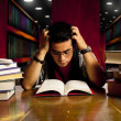 Young adult student reads book at library — Stock Photo