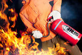 Fireman fighting a raging fire with big flames — ストック写真