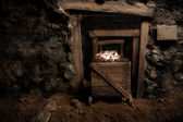Inside of an old mine with mining cart full of brilliant stones — Stock Photo