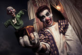 Photo of a scary clown holding a Jack-in-the-box toy — Stock Photo