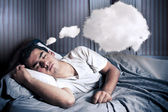 Man comfortably dreaming in his bed with a cloud — Stock Photo