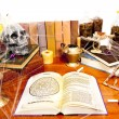 Table full of witchcraft related objects and cobwebs isolated on white - Stock Photo