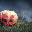 Jack-o-lantern in a graveyard at night - Stock Photo