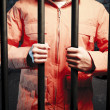 Inmate inside dark prison cell at night - Stock Photo