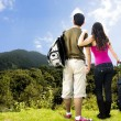 Beautiful Couple looking afar from the top of a mountain - Stock Photo
