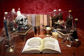 Table full of witchcraft related objects and cobwebs — Stock Photo
