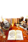 Table full of witchcraft related objects and cobwebs isolated on white — Stock Photo