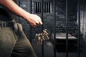 Prison guard with keys walking outside dark prison cell — Stock Photo