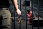 Gardien de la prison avec des clés à l'extérieur de la cellule de prison sombre — Photo