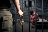 Prison guard with keys outside dark prison cell — Stock Photo