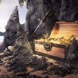 Open treasure chest with bright gold in a cave — Stock Photo #11605001