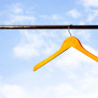 Wooden coat hanger against blue sky — Stock Photo