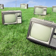 Field of grass with retro tv's — Stock Photo