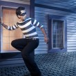 Thief walking on the roof of a house at night - Stock Photo