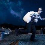 dief op het dak lopen 's nachts — Stockfoto