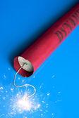 Lit dynamite stick on a blue background — Stock Photo