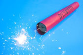 Lit dynamite stick on a blue background — Stock Photo