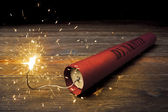 Lit dynamite stick on the floor — Stock Photo