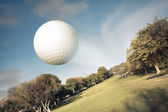 Golf ball flying over the field — Stock Photo