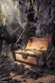 Open treasure chest with bright gold in a cave — Stok fotoğraf