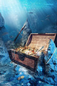 Open treasure chest with bright gold underwater — Stok fotoğraf