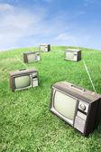 Field of grass with retro tv's — Fotografia Stock