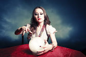 Pretty fortuneteller with her crystal ball on a seance sesion — Stockfoto