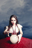 Pretty fortuneteller with her crystal ball on a seance sesion — Stock Photo