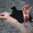 Two hands make their way through the broken glass — Stock Photo