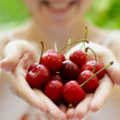 Smiling girl holding a handful of red cherries — Stock Photo #12132595