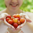 She holds a handful of cherries — Stock Photo