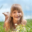 The llaughing girl is lying on the grass — Stock Photo