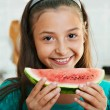 The smiling girl is eating the watermelon — Stock Photo