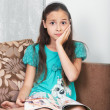 The upset girl is sitting on the sofa — Stock Photo