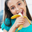 Cute girl eats an banana — Stock Photo