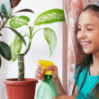 Girl irrigate flower — Stock Photo