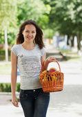 La joven sonriente con la cesta — Foto de Stock
