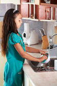 Girl washing dishes in the kitchen — Stock Photo