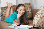 The smiling girl reading on the sofa — Stock Photo