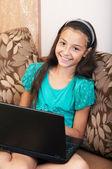 La niña sentada en el sofá con el ordenador portátil — Foto de Stock