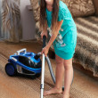 The girl is vacuuming the carpet — Stock Photo