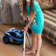 The girl is vacuuming the carpet — Stock Photo #12392390