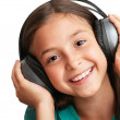 The smiling girl is holding the headphones — Stock Photo #12392543