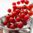 Cherry Tomatoes Tumbling Into Metal Colander — Stock Photo #11944045