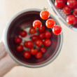 Cherry Tomatoes Tumbling From Metal Colander Into Metal Pan — Stock Photo #11944075